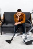 Aufgebrachter Mann im modernen Wohnzimmer sitzt auf Sofa und blickt auf Staubsauger