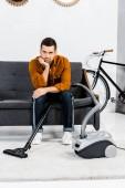 Aufgebrachter Mann in modernem Wohnzimmer sitzt auf Sofa und blickt in Kamera