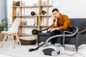 Aufgebrachter Mann im modernen Wohnzimmer sitzt auf Sofa neben Staubsauger und blickt in Kamera