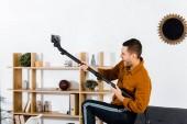 schöner Mann im modernen Wohnzimmer spielt mit Staubsauger