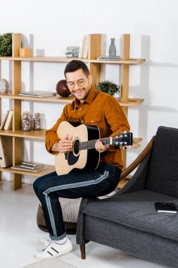 cheerful man in glasses playing acoustic guitar while sitting on sofa at home