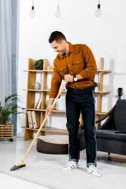 handsome man cleaning carpet with broom in modern living room