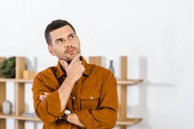 handsome man standing in modern living room doing thinking gesture