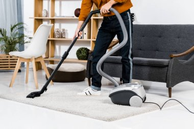 cropped view of man in modern living room cleaning house with hoover