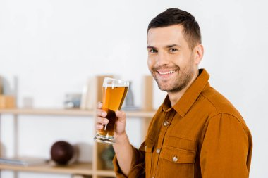 Handsome man in modern living room holding glass of beer and looking at camera stock vector