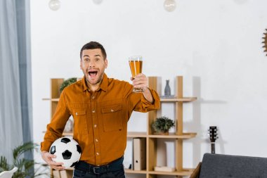 Handsome man in modern living room screaming while holding football ball and glass of beer stock vector