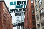 Fotografie Městská scéna s budovami, brooklyn bridge a nápis staré způsoby nelze otevřít nové dveře v new york city, usa