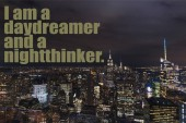 aerial view of buildings and night city lights with i am a daydreamer and a nightthinker lettering in new york, usa