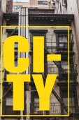 urban scene with old building in new york with yellow city lettering in frame, usa