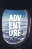 pohled z modré oblohy jasno od letadla s nápisem dobrodružství na okně