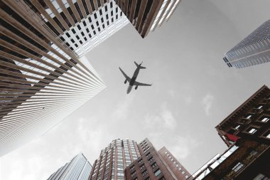 bottom view of skyscrapers and airplane in cloudy sky in new york city, usa