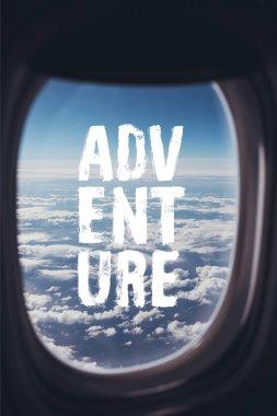 """Картина, постер, плакат, фотообои """"вид голубого облачного неба с самолета с надписью """"приключение"""" на окне картины"""", артикул 236165506"""