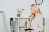Photo side view of thoughtful mature businesswoman holding notebook and looking away in office