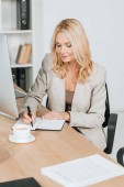 smiling mature businesswoman writing in notebook while sitting at workplace