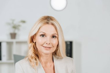portrait of beautiful blonde mature businesswoman smiling at camera in office