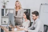 Fotografie Reife Geschäftsfrau hält Ordner und mit Blick auf junge Geschäftsleute, die im Büro arbeiten