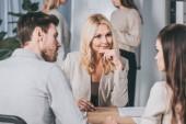 bella mentore di affari sorridente seduto con la mano sul mento e guardando giovani colleghi in ufficio