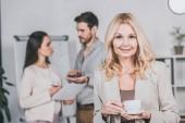 gyönyörű érett üzletasszony gazdaság csésze kávét, és mosolyogva kamera, míg fiatal kollégák megvitatása mögött hivatalban