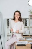 krásné šťastná mladá podnikatelka držící šálek kávy a usmívá se na kameru v úřadu