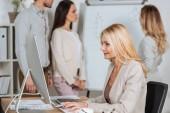 Fotografie Seitenansicht des lächelnden Geschäftsfrau mit Desktop-Computer und junge Kolleginnen und Kollegen arbeiten mit Whiteboard hinter