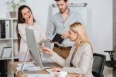 professioneller Business-Mentor zeigt auf Desktop-Computer und arbeitet mit gelangweilten jungen Kollegen im Büro