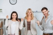 Photo cheerful professional business colleagues shaking fists and smiling at camera in office