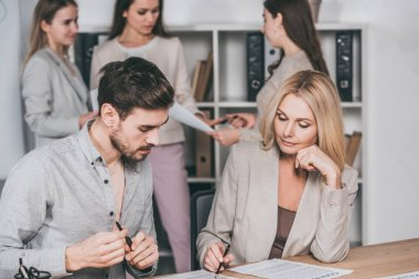 professional mentor working with young businessman, businesswomen standing behind in office
