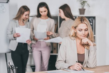 mature businesswoman working with contract and young businesswomen discussing papers behind in office