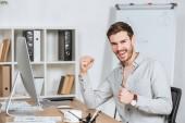 šťastný mladý podnikatel triumfovat a usmívá se na kameru v úřadu