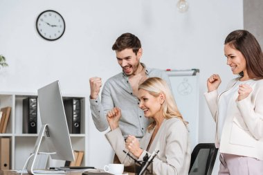 excited business mentor with colleagues shaking fists and looking at desktop computer in office
