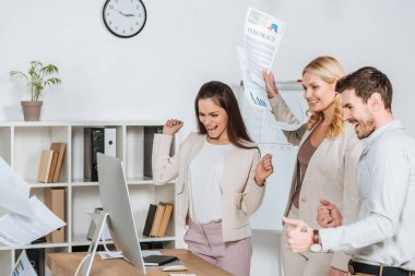 excited businesspeople shaking fists and looking at desktop computer in office