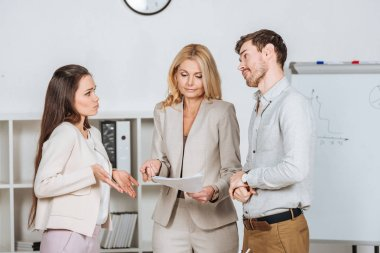 female mentor holding papers and working with frustrated young colleagues in office