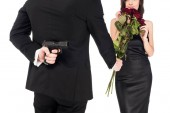 back view of man gifting red roses while hiding gun behind the back, isolated on white