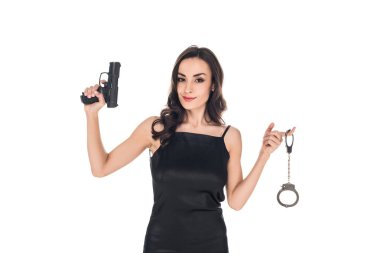 Attractive smiling secret agent in black dress holding gun and handcuffs, isolated on white stock vector