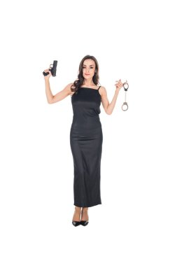 Beautiful female secret agent in black dress holding gun and handcuffs, isolated on white stock vector