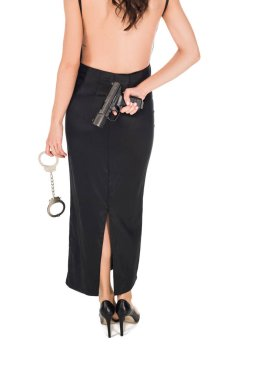 cropped view of female secret agent in black dress holding handgun and handcuffs, isolated on white