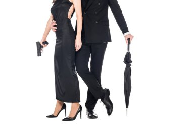 cropped view of couple of killers in black clothes holding gun and umbrella, isolated on white