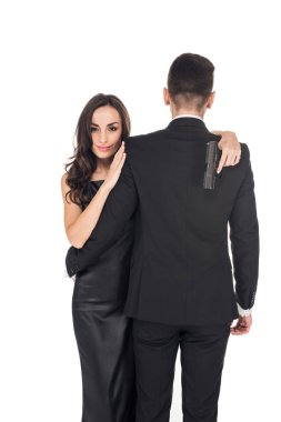 beautiful couple of secret agents hugging and holding handgun, isolated on white