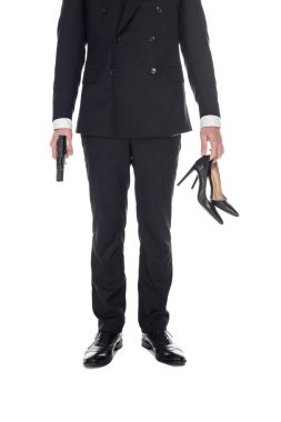cropped view of secret agent in black suit holding handgun and high heels, isolated on white