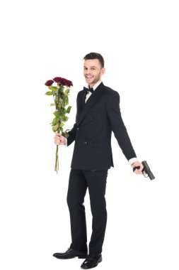 Smiling secret agent in black suit holding handgun and red roses, isolated on white stock vector