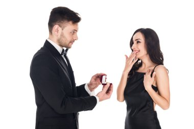happy boyfriend giving proposal ring in box to surprised girlfriend, isolated on white
