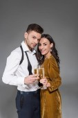 young smiling couple hugging and holding champagne glasses isolated on grey