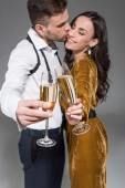 Fotografie selective focus of kissing couple clinking with champagne glasses isolated on grey