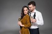 junges glückliches Paar umarmt und hält Champagnergläser isoliert auf grau