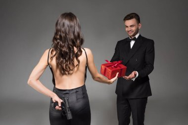 woman gifting red present to man while hiding gun behind the back, isolated on grey