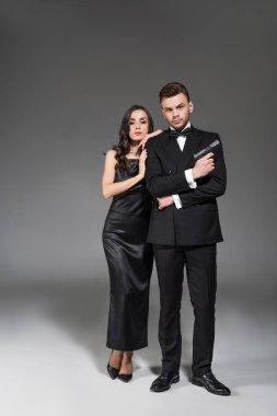 elegant couple of secret agents with handgun on grey