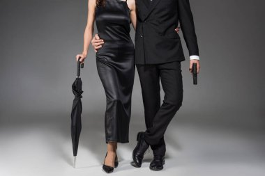 cropped view of young couple of killers in black clothes posing with gun and umbrella on grey
