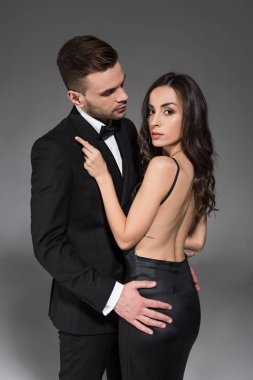 elegant couple in black clothes hugging together isolated on grey