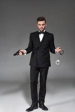 Elegant secret agent in tuxedo holding handgun and handcuffs on grey stock vector
