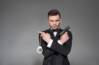 Serious secret agent in black tuxedo holding gun and handcuffs, isolated on grey stock vector